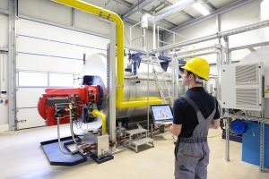 Techniker kontrolliert Heizungsanlage in d. Industrie